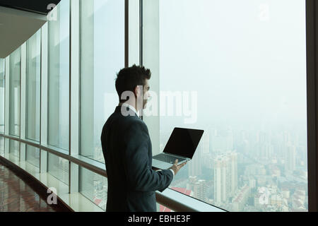 Young businessman with laptop looking out of skyscraper office window, Shanghai, China - Stock Photo