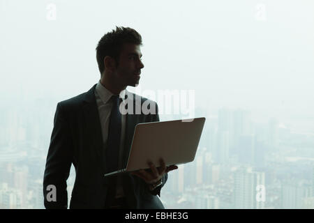 Young businessman with laptop in front of skyscraper office window, Shanghai, China - Stock Photo
