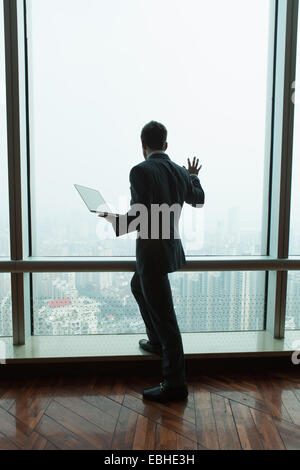 Young businessman with laptop looking down from skyscraper office window, Shanghai, China - Stock Photo