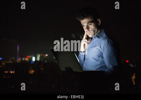 Young businessman looking at laptop in front of skyscraper office window at night, Shanghai, China - Stock Photo