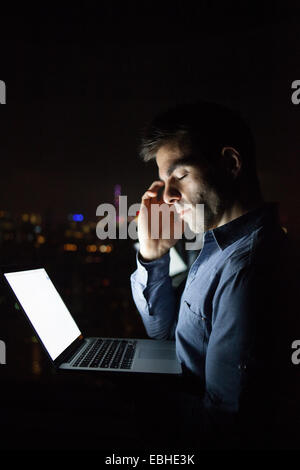 Tired young businessman with laptop in front of skyscraper office window at night, Shanghai, China - Stock Photo