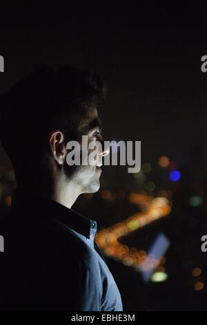 Close up of young businessman looking out of skyscraper office window at night, Shanghai, China - Stock Photo