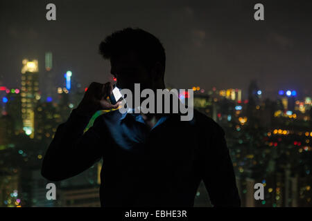 Silhouetted young businessman chatting on smartphone in front of skyscraper office window at night, Shanghai, China - Stock Photo