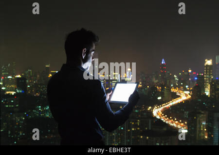 Silhouetted young businessman looking at digital tablet in front of skyscraper office window at night, Shanghai, - Stock Photo