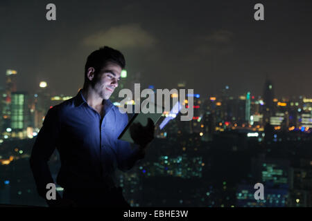 Young businessman looking at digital tablet in front of skyscraper office window at night, Shanghai, China