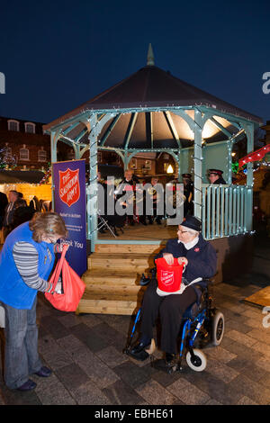 Salvation Army brass band with disabled lady collector collecting cash. Christmas market in Market Place Salisbury, - Stock Photo