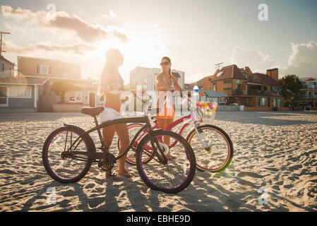 Two women cyclists chatting on beach, Mission Bay, San Diego, California, USA - Stock Photo
