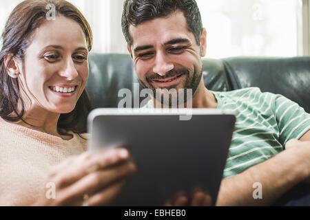 Couple using digital tablet on sofa - Stock Photo