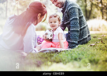 Parents and daughter playing in garden - Stock Photo