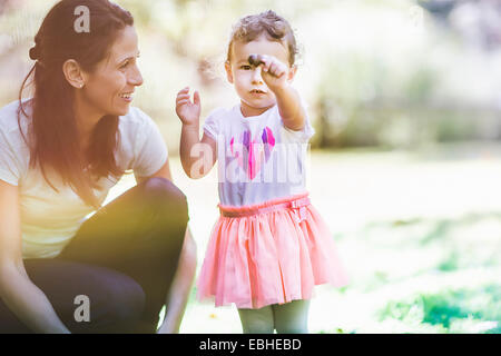 Mother and daughter playing in garden - Stock Photo