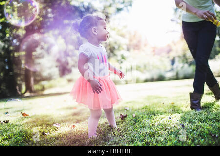Mother and daughter playing bubbles in garden - Stock Photo