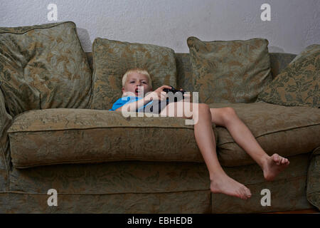 Boy playing video game in living room - Stock Photo
