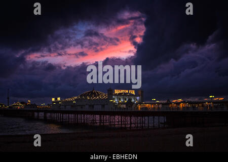 Storm clouds and sunset over Brighton Pier - Stock Photo