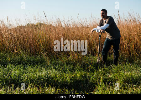 Portrait of mid adult male farmer leaning on spade in field, Plattsburg, Missouri, USA - Stock Photo