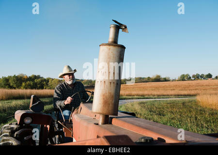 Senior male farmer driving tractor on rural road, Plattsburg, Missouri, USA - Stock Photo