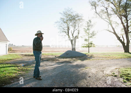 Senior male farmer chatting on smartphone on dirt track, Plattsburg, Missouri, USA - Stock Photo