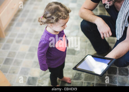 Father and daughter using digital tablet in kitchen - Stock Photo