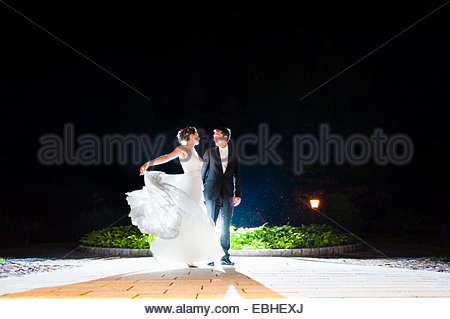 Romantic newlywed mid adult couple dancing in garden at night - Stock Photo
