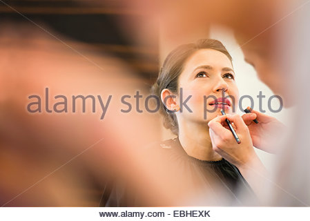 Female friend applying lip liner to brides lips - Stock Photo