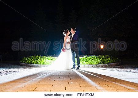 Romantic newlywed mid adult couple illuminated in garden at night - Stock Photo