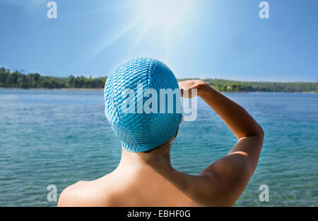Rear view of young woman in blue swimming cap gazing out to sea, Milna, Brac, Croatia - Stock Photo