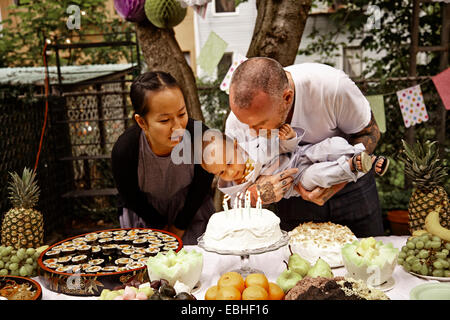 Parents and male toddler having birthday party in garden - Stock Photo