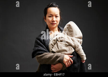 Studio portrait of mid adult woman holding baby son - Stock Photo