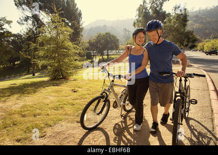 Mature couple chatting whilst pushing bicycles in park - Stock Photo