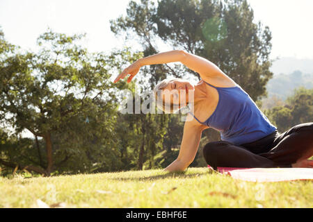 Mature woman practicing yoga in park - Stock Photo