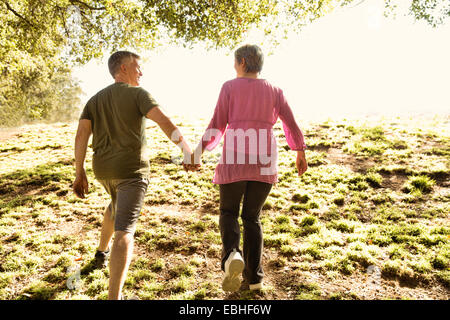 Rear view of mature couple power walking in park - Stock Photo