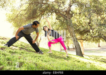 Mature running couple warming up together in park - Stock Photo