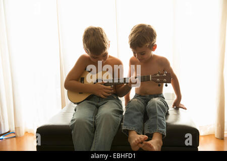 Brothers playing guitar at home - Stock Photo
