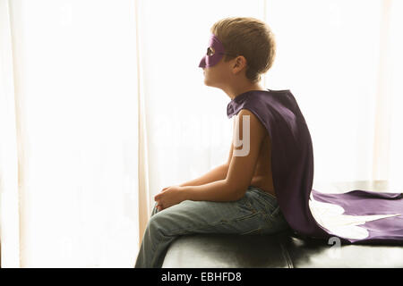 Boy in cape and mask at home - Stock Photo