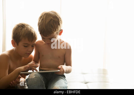 Brothers using digital tablet at home - Stock Photo