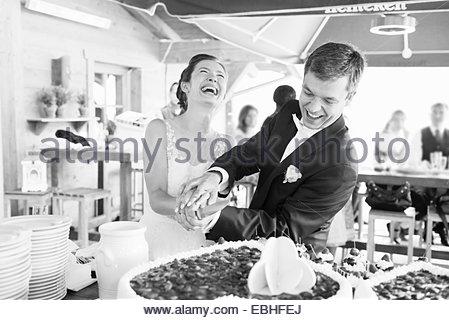 Black and white shot of bride and bridegroom cutting wedding cake - Stock Photo