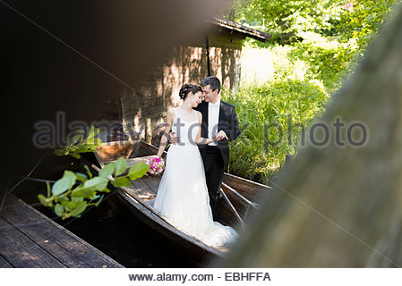 Romantic newlywed mid adult couple standing in rowing boat - Stock Photo
