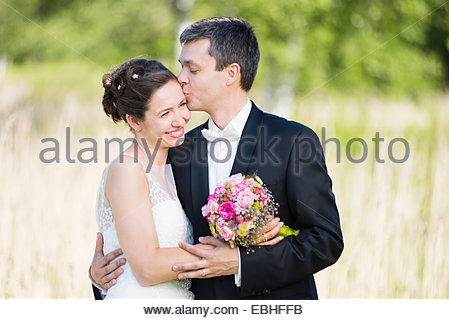 Portrait of romantic newlywed mid adult couple in park - Stock Photo