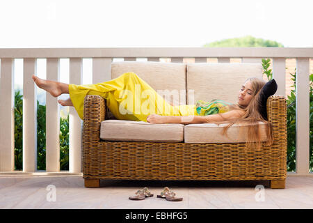 Young woman asleep on balcony sofa, Milna, Brac, Croatia - Stock Photo