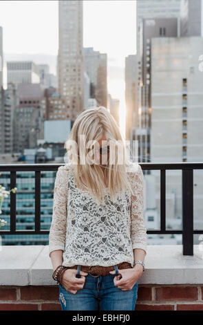 Young woman with city view in background - Stock Photo