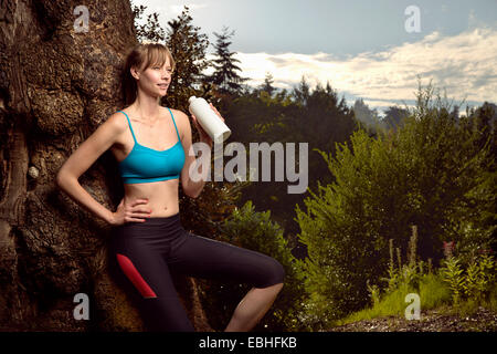 Female runner leaning against rock in park drinking water - Stock Photo
