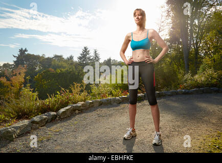 Portrait of female runner with hands on hips in park - Stock Photo