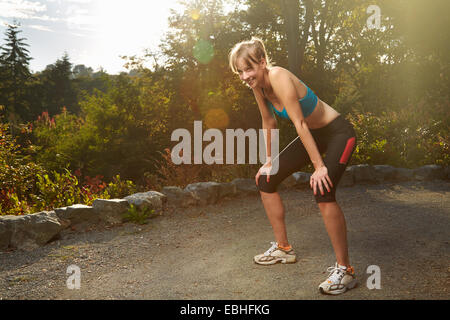 Exhausted female runner taking a break in park - Stock Photo