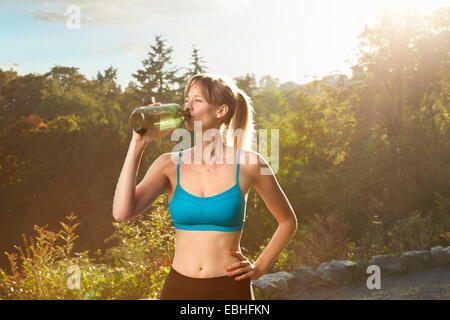Mid adult female runner taking a water break in park - Stock Photo