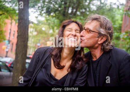 Portrait of romantic mature couple on city street - Stock Photo