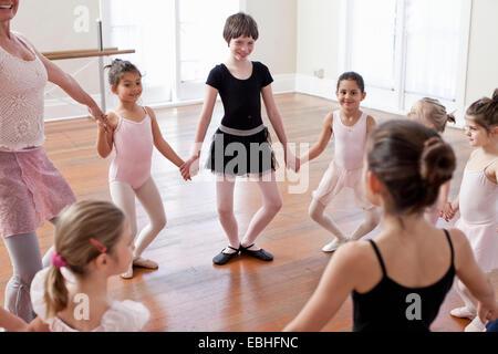 Children and teacher in a circle practicing ballet in ballet school - Stock Photo