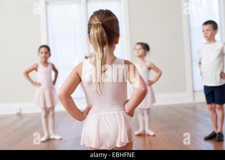 Four children practicing ballet with hands on hips in ballet school - Stock Photo