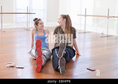 Two teenage girls chatting in ballet school - Stock Photo