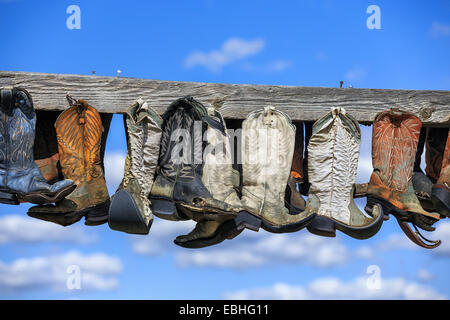 Old cowboy boots hanging on post, in memory of John Booth, Great Sandhills, near Sceptre, Saskatchewan, Canada - Stock Photo