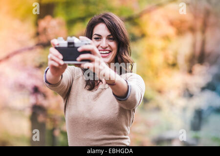 Young woman taking selfie with SLR camera in autumn forest - Stock Photo