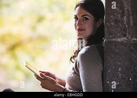 Portrait of young woman leaning against wall using digital tablet - Stock Photo